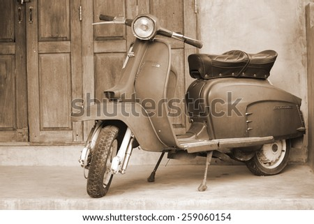 CHIANG MAI,THAILAND-FEB22 : old vespa parked in front of a house for show (post process to be sepia style picture).,On Feb 22, 2015 in Chiang Mai, Thailand. - stock photo