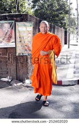 CHIANG MAI, THAILAND - February 03, 2014: A Buddhist monk goes around for the streets looking for offers in Chiang mai, Thailand.  - stock photo