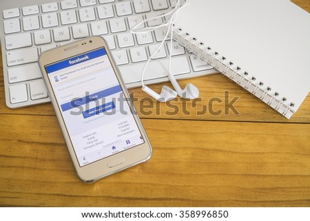 CHIANG MAI ,THAILAND - Jan 1, 2016: Young man touch Facebook icons  Facebook is largest and most popular social networking site in the world. - stock photo