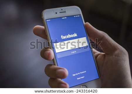 CHIANG MAI, THAILAND - JANUARY 02, 2015: A man trying to log in Facebook application using Apple iPhone 6. Facebook is largest and most popular social networking site in the world. - stock photo