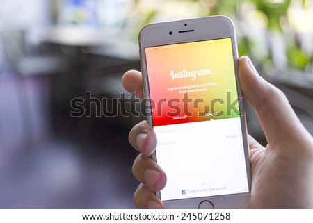 CHIANG MAI, THAILAND - JANUARY 02, 2015: A man trying to log in Instagram application using Apple iPhone 6. Instagram is largest and most popular photograph social networking site in the world.