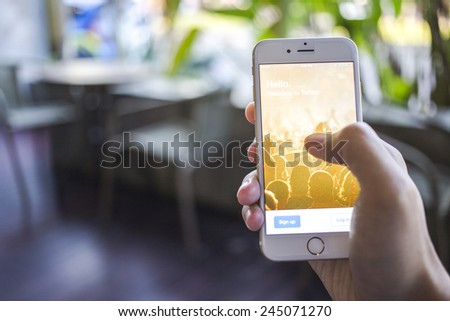 CHIANG MAI, THAILAND - JANUARY 02, 2015: A man trying to log in Twitter application using Apple iPhone 6. Twitter is largest and most popular social networking site in the world. - stock photo