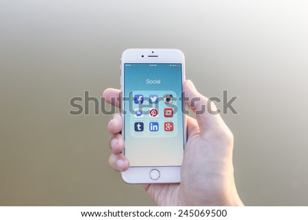 CHIANG MAI, THAILAND - JANUARY 02, 2015: All of popular social media icons on smartphone device screen with hand holding on Apple iPhone 6. - stock photo
