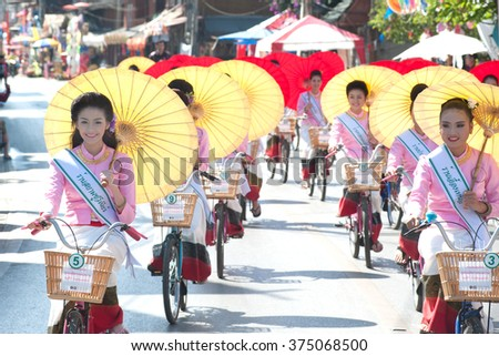 CHIANG MAI, THAILAND-JANUARY 16,2016 : Group of women in traditional costume hold umbrella and ride bicycle parade show in 33th anniversary Bosang umbrella festival,San Kampaeng, Chiang Mai, Thailand.