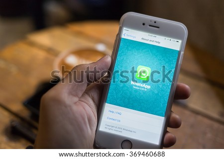 CHIANG MAI, THAILAND - JANUARY 25, 2016: Man try to use social Internet service WhatsApp screen on blue background. iPhone 6S was created and developed by the Apple inc. - stock photo