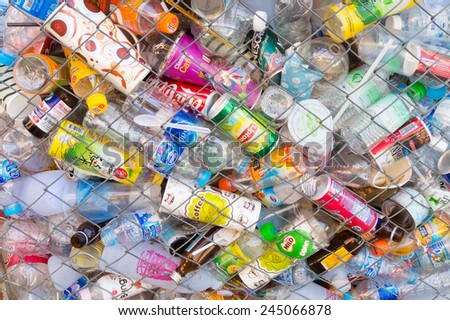 CHIANG MAI, THAILAND - JANUARY 14, 2015: plastic bottles and drink can in a metal cage on a recycle factory in Chiang Mai, Thailand. The plastic and aluminium can will be sorted for recycling. - stock photo