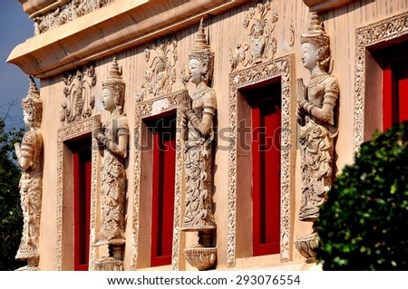 Chiang Mai, Thailand - January 3, 2013:  Thai Khong figures with hands clasped in prayer decorate the base of the remarkable Repository Library at Wat Phra Singh  *