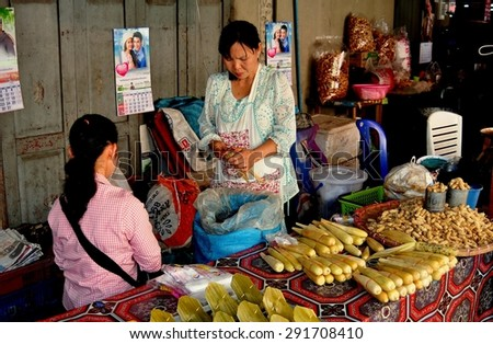 Chiang Mai, Thailand - January 2, 2013:  Two Thai women selling bamboo, peanuts, and other exotic foods at the Somphet Market
