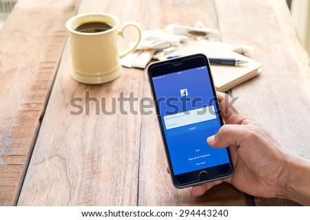 CHIANG MAI ,THAILAND - JULY 08, 2015: Young man touch Facebook icons on Apple iPhone 6 plus. Facebook is largest and most popular social networking site in the world. - stock photo