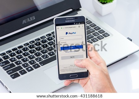 CHIANG MAI,THAILAND - JUN 4, 2016 : Woman holding Samsung galaxy Alpha with paypal app on the screen on white desk office. Top view of Business workplace.