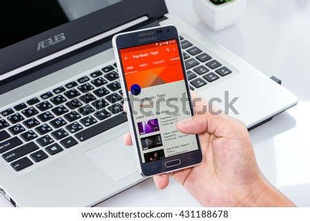 CHIANG MAI,THAILAND - JUN 4, 2016 : Woman holding Samsung galaxy Alpha with youtube app on the screen on white desk office. Top view of Business workplace.