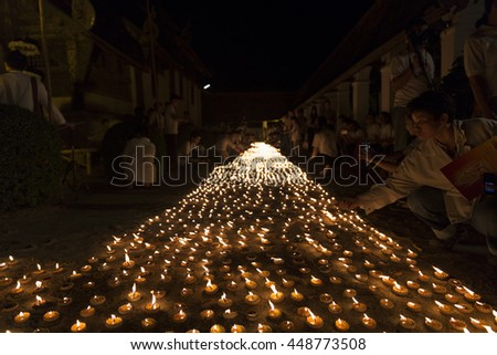 Chiang Mai, Thailand - June 10, 2016: People light candle to pay respect to buddha relic at Tonkwen temple in Chiang Mai, Thailand on June 10, 2016.