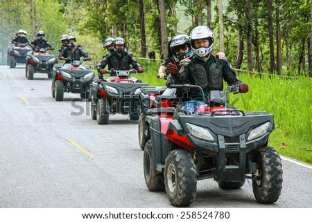 CHIANG MAI, THAILAND - JUNE 10 : Tourists riding ATV to nature adventure on dirt track on JUNE 10, 2014 in Chiang Mai, Thailand.  - stock photo