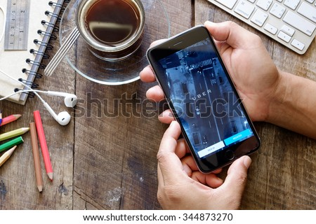 CHIANG MAI,THAILAND, NOV - 29 -2015 : male hands holding iPhone 6 plus showing  Uber app on screen ,Uber is smartphone app-based transportation network.  - stock photo