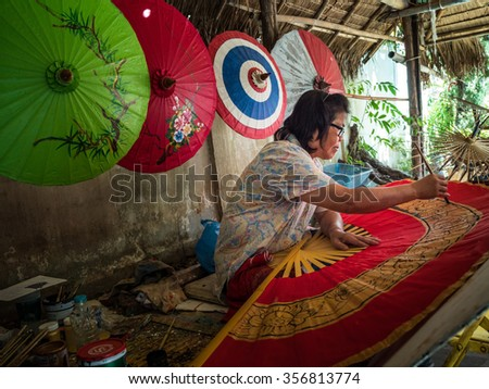 CHIANG MAI, THAILAND - NOVEMBER 22, 2015: An unidentified woman paints on a giant fan in cottage factory in Chiang Mai, Thailand. This is a traditional craft that attracts local and foreign visitors. - stock photo
