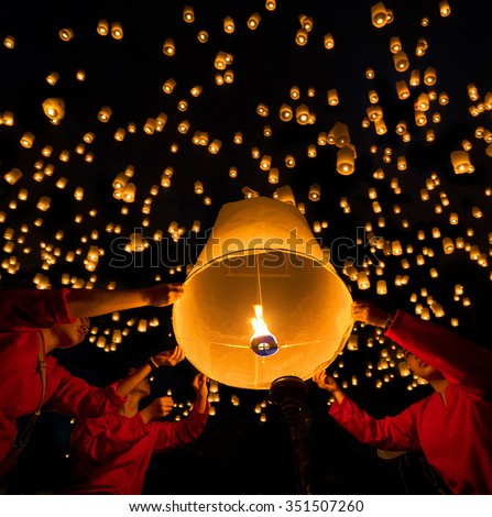 CHIANG MAI, THAILAND - NOVEMBER 25, 2015: Buddhist devotees release 'sky lanterns' into the night skies in the 'Loy Krathong' celebrations. This event is also known as the 'Yeeping Lanna' Festival. - stock photo