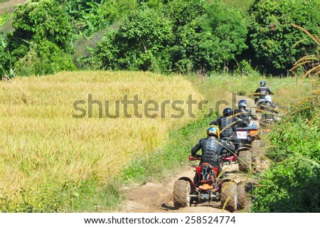 CHIANG MAI, THAILAND - NOVEMBER 24 : Tourists riding ATV to nature adventure on dirt track on NOVEMBER 24, 2013 in Chiang Mai, Thailand.  - stock photo