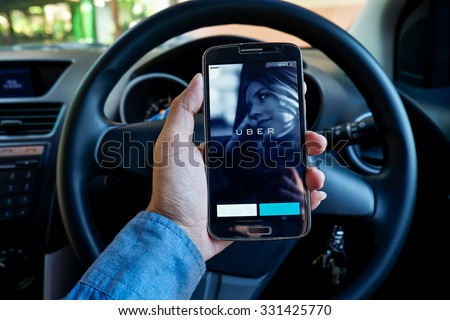 CHIANG MAI,THAILAND - OCT 26,2015 : A man hand holding Uber app showing on Samsung in the car,Uber is smartphone app-based transportation network. - stock photo