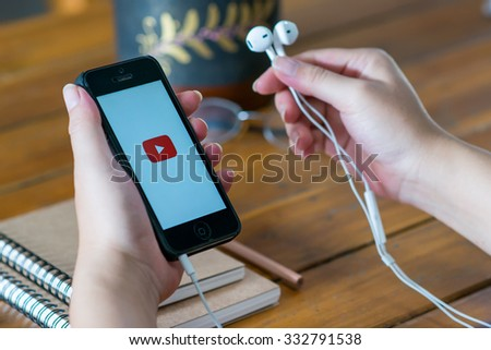 CHIANG MAI,THAILAND - October 29, 2015: Brand Apple iPhone 5  with YouTube app on the screen lying on old wood desk with headphones. YouTube is the popular online video sharing website - stock photo