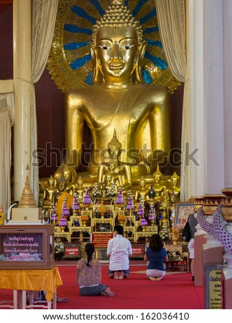 Chiang Mai, Thailand - October 25, 2013: Buddhist devotees praying in main temple at Wat Phra Singh in Chiang Mai, Thailand. - stock photo