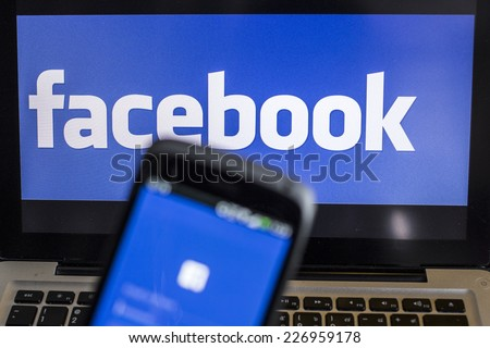 CHIANG MAI, THAILAND - OCTOBER 21, 2014: Facebook application sign in page on smartphone and facebook logo on background. Facebook is largest and most popular social networking site in the world. - stock photo