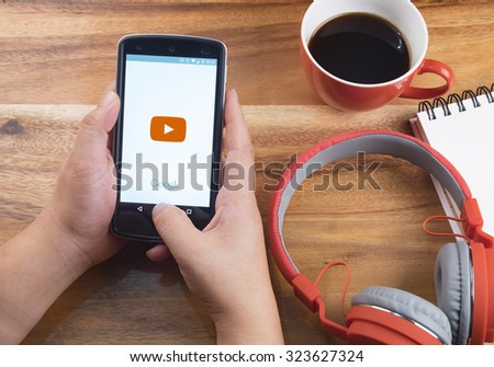 CHIANG MAI, THAILAND -October 4, 2015:LG Nexus 5 open YouTube app on the screen lying on desk with headphones. YouTube is the popular online video-sharing website. - stock photo