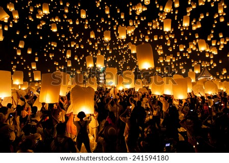 CHIANG MAI, THAILAND � OCTOBER 25, 2014: People release sky lanterns to pay homage to the buddhist triple gem: Budhha, Dharma and Sangha, during Yi Peng festival in Chiang Mai near Mae Jo University. - stock photo