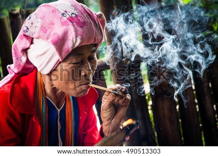Chiang Mai, Thailand, - October, 23, 2014 : Unidentified name old tribal women wearing a traditional tribal sitting smoking happily at Doi Inthanon Chiang Mai Thailand