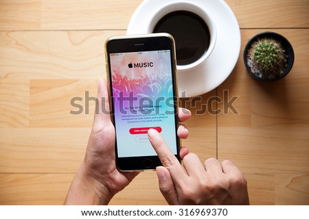 CHIANG MAI,THAILAND - SEP 16,2015 : A woman hand holding Apple music app showing on iPhone 6 plus. Apple Music is the new iTunes-based music streaming service that arrived on iPhone, - stock photo