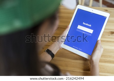 CHIANG MAI, THAILAND - SEPTEMBER 07, 2014: A girl trying to log in Facebook application using Apple iPad Air. Facebook is largest and most popular social networking site in the world. - stock photo