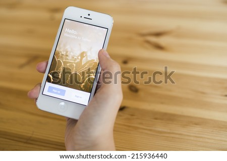 CHIANG MAI, THAILAND - SEPTEMBER 07, 2014: A girl trying to log in Twitter application using Apple iPhone 5. Twitter is largest and most popular social networking site in the world. - stock photo