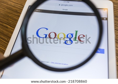 CHIANG MAI, THAILAND - SEPTEMBER 17, 2014: Magnifying glass of Google search page view on web browser Apple iPad Air device. - stock photo