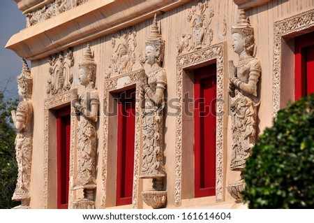 CHIANG MAI, THAILAND:  Thai sttues with hands clasped in prayer decorate the base of the remarkable Repository Library at Wat Phra Singh