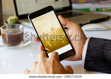 CHIANG MAI, THAILND, DEC - 08 - 2015 : A man trying to log in Twitter application using Apple iPhone 6. Twitter is largest and most popular social networking site in the world. - stock photo