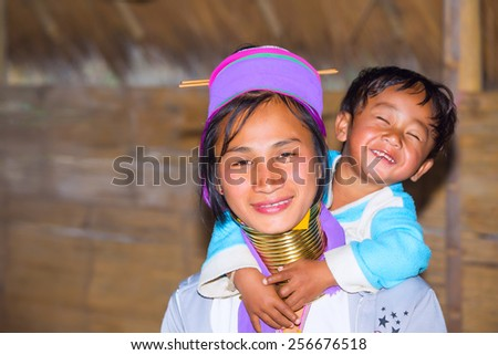 CHIANG RAI, THAILAND - JAN 2015: Karen tribal woman with her child near Mae Hong Son, Thailand, Chiang Rai. Padaung long neck hill tribe village, refugee community originate from neighboring Myanmar. - stock photo