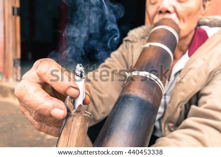 "CHIANG RAI, THAILAND - JUNE 12 2016: Unidentified man hill tribes of Thai smoking tobacco by strip bamboo in Chiang Rai, Thailand. ""Hmong"" is hill tribes that live on the high mountain."