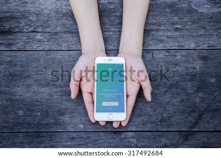 CHIANG RAI, THAILAND - SEPTEMBER 13, 2015:  Woman try to login to Twitter application on Apple iPhone 6 blue background. Twitter is largest and most popular social networking site in the world. - stock photo