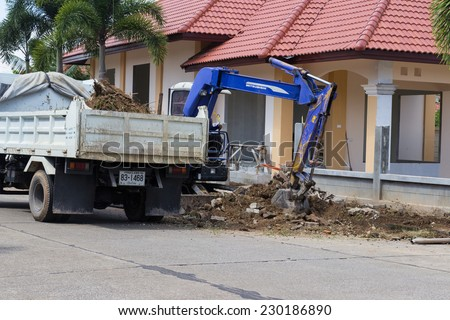CHIANGMAI, SEPTEMBER 28: The worker controls the backhoe shovel to load the soil on the ground to unload on the truck on September 28, 2014 in Chiangmai, Thailand. - stock photo
