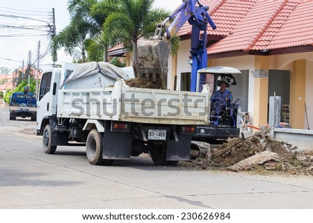 CHIANGMAI, SEPTEMBER 28: worker controls the backhoe shovel to unload the earth on the truck on September 28, 2014 in Chiangmai, Thailand. - stock photo