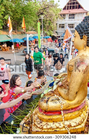 CHIANGMAI, THAILAND - APRIL 14: People pouring water to Buddha Phra Singh at Phra Singh temple in Songkran festival on April 14, 2010 in Chiang Mai, Thailand. - stock photo