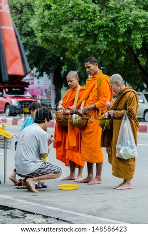 CHIANGMAI, THAILAND - AUGUST 4 :Buddhist monks blessing a buddhist after received food from him . August 4, 2013 In Chiangmai, Thailand.