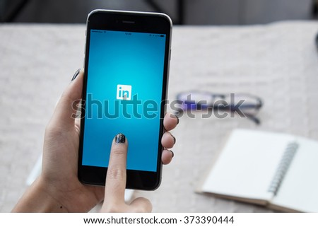 CHIANGMAI,THAILAND - FEB 2 ,2016:Woman holding iPhone 6 plus with social network service LinkedIn on the screen. iPhone 6 plus was created and developed by the Apple inc. - stock photo