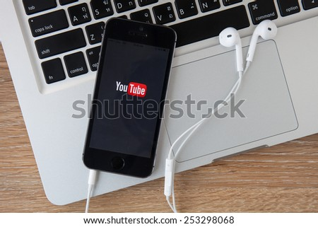 CHIANGMAI,THAILAND - FEBRUARY 17, 2015: Brand new Apple iPhone 6 with YouTube app on the screen lying on desk with headphones. YouTube is the popular online video-sharing website, - stock photo
