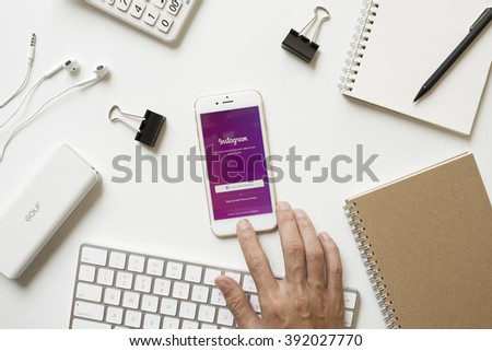 CHIANGMAI, THAILAND - FEBRUARY 16, 2016: Man hand touching on Apple iPhone 6s button and open Instagram iOS app on office desk. Instagram is photo-sharing social network. - stock photo