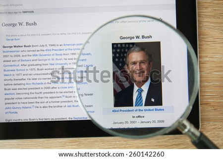 CHIANGMAI, THAILAND - February 26, 2015: Photo of Wikipedia article page about George W. Bush  on a ipad monitor screen through a magnifying glass. - stock photo