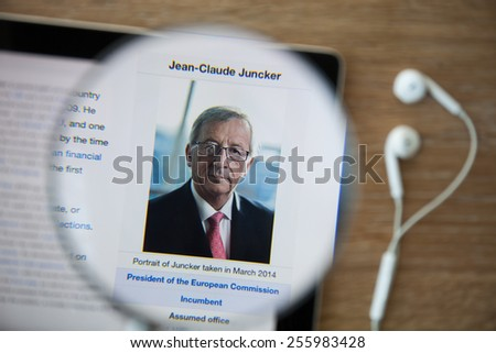 CHIANGMAI, THAILAND - February 26, 2015: Photo of Wikipedia article page about Jean-Claude Juncker on a ipad monitor screen through a magnifying glass. - stock photo