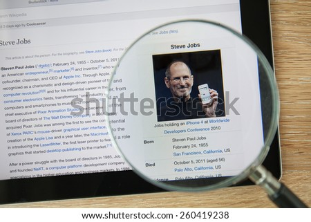 CHIANGMAI, THAILAND - February 26, 2015: Photo of Wikipedia article page about Steve Jobs on a ipad monitor screen through a magnifying glass. - stock photo