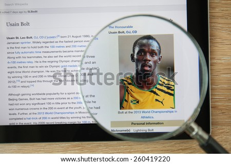 CHIANGMAI, THAILAND - February 26, 2015: Photo of Wikipedia article page about Usain Bolt on a ipad monitor screen through a magnifying glass. - stock photo