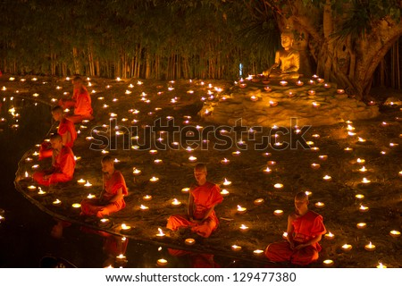 CHIANGMAI, THAILAND - FEBRUARY 25:  Unidentified Thai monks meditate around buddha statue among many lanterns at Phan Tao temple in Magha Puja Day on February 25, 2013 in Chiang Mai, Thailand. - stock photo