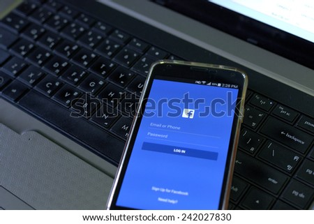 CHIANGMAI, THAILAND - January 3, 2015: Facebook application sign in page on smartphone put on the notebook. Facebook is largest and most popular social networking site in the world. - stock photo